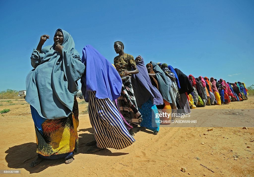 Displaced Somalis queue for aid in Beledweyne, north of Mogadishu on May 26, 2016. Hundreds of families have been forced out of their homes following flash floods in Beledweyne after torrential rains pounded the area in the last few days.The heavy rains led to the bursting of River Shabelle which caused massive floods in residential areas along the river. / AFP / MOHAMED