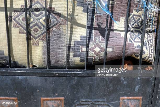 TOPSHOT A displaced Syrian child looks out from behind a gate in Raqa's western alSabahiya district where they are taking shelter on August 14 2017...