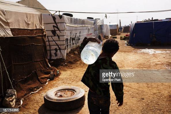 A displaced Syrian child walks through a camp with a jug of water in a makeshift camp for Syrian refugees only miles from the border with Syria in...