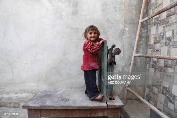 TOPSHOT A displaced Syrian girl from the town of Maidaa plays outside her home in the town of Mesraba in the eastern Ghouta region a rebel stronghold...