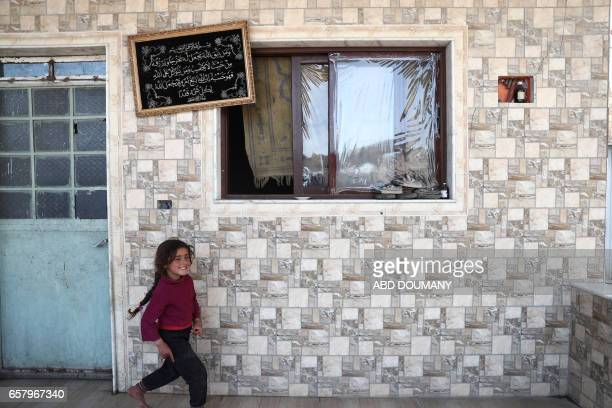 A displaced Syrian girl from the town of Maidaa plays outside her home in the town of Mesraba in the eastern Ghouta region a rebel stronghold east of...