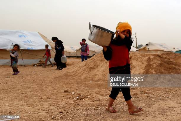 TOPSHOT A displaced Syrian girl walks holding a pot at the alMabrouka camp in the village of Ras alAin on the SyriaTurkey border where many Syrians...