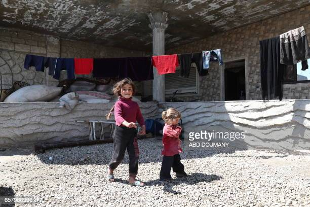 Displaced Syrian girls from the town of Maidaa play outside their home in the town of Mesraba in the eastern Ghouta region a rebel stronghold east of...