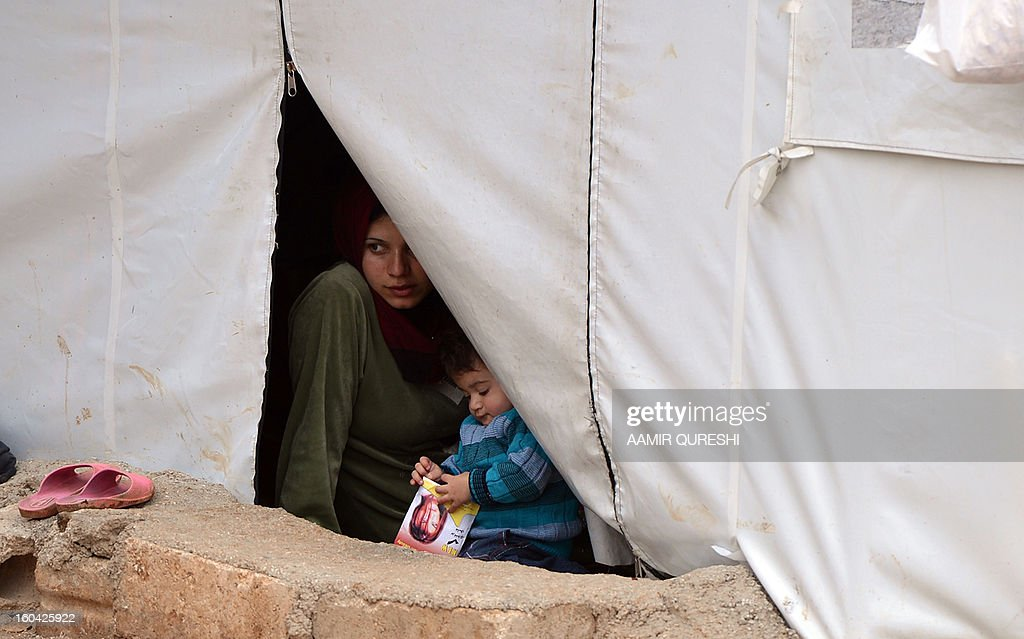 A Displaced Syrian looks out from her tent at the refugee camp of Qah along the Turkish border in the village of Atme in the northwestern province of Idlib, on January 31 2012. Syria's main opposition group was to meet in Cairo, a day after a surprise statement from its chief that he was willing to hold talks with regime officials, a Syrian National Coalition member said. AFP PHOTO/AAMIR QURESHI