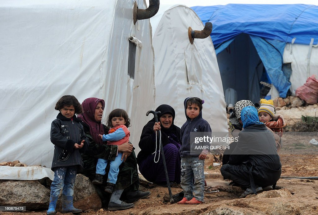 Displaced Syrian people gather outside their tents at the refugee camp of Qah along the Turkish border in the village of Atme in the northwestern province of Idlib, on February 7, 2013. More than half of the estimated 300,000 Syrian refugees who have fled to Lebanon are not receiving the medical treatment they need because of high costs, Doctors Without Borders (MSF) said.