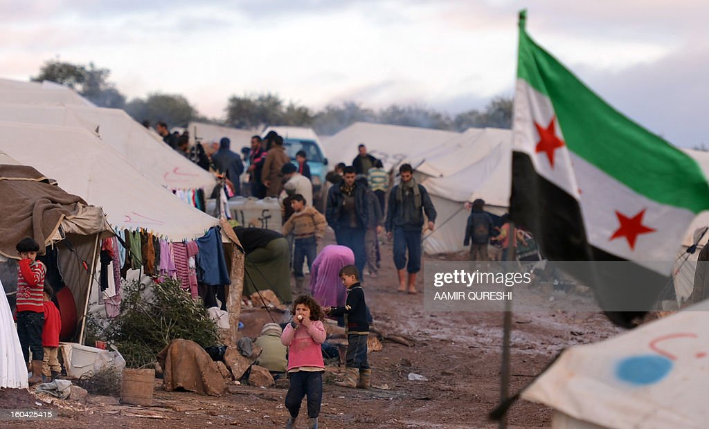 Displaced Syrian refugees gather outside their tents at the refugee camp of Qah along the Turkish border in the village of Atme in the northwestern province of Idlib, on January 31 2012. Syria's main opposition group was to meet in Cairo, a day after a surprise statement from its chief that he was willing to hold talks with regime officials, a Syrian National Coalition member said.
