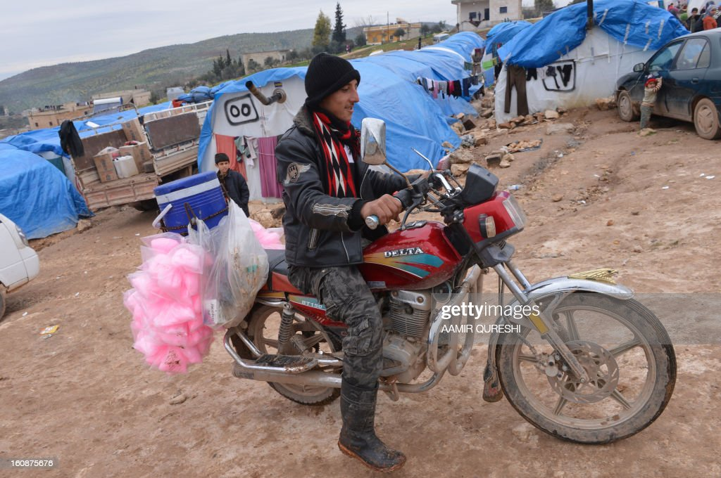 A displaced Syrian vendor sits on his motorcycle as he wait for customers at the refugee camp of Qah along the Turkish border in the village of Atme in the northwestern province of Idlib, on February 7, 2013. More than half of the estimated 300,000 Syrian refugees who have fled to Lebanon are not receiving the medical treatment they need because of high costs, Doctors Without Borders (MSF) said.