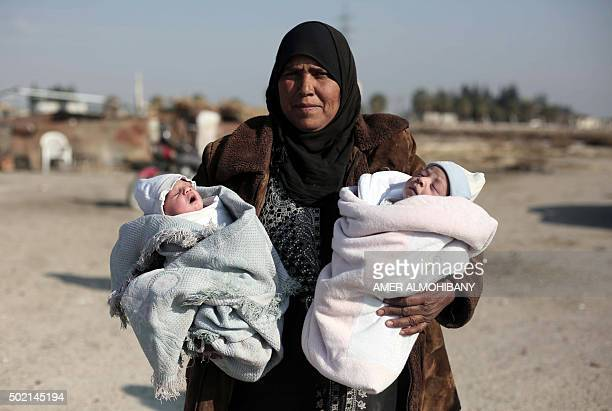 A displaced Syrian woman from the disputed area of Marj alSultan east of Damascus holds her tendayold twin grandchildren who are lacking milk in the...