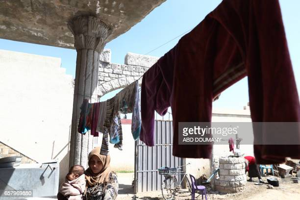 A displaced Syrian woman from the town of Maidaa sits with a child outside her home in the town of Mesraba in the eastern Ghouta region a rebel...