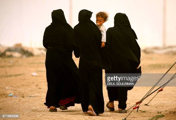 TOPSHOT Displaced Syrian women walk at the alMabrouka camp in the village of Ras alAin on the SyriaTurkey border where many Syrians who fled from...