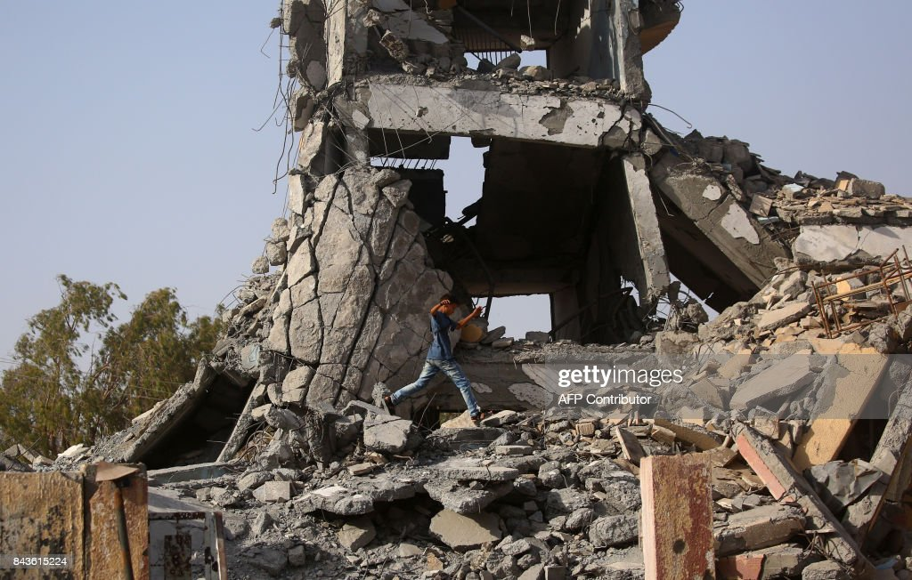 TOPSHOT - A displaced Syrian youth who fled the Islamic State (IS) group's Syrian stronghold of Raqa as fighters from a US-backed coalition battle to retake the city, walks above the rubble of a destroyed building in the town of Tabqa, about 55 kilometres (35 miles) west of embattled city on September 6, 2017. The Islamic State group has already lost more than half of its bastion of Raqa to attacking US-backed forces. / AFP PHOTO / Delil souleiman