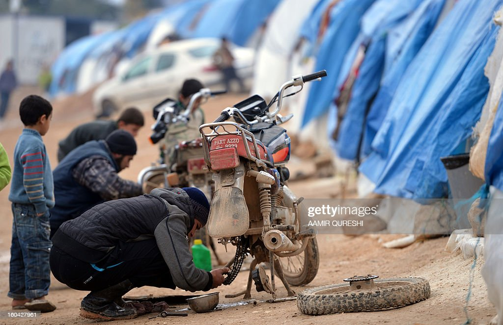 Displaced Syrians repair their motorbikes at the refugee camp of Qah along the Turkish border in the village of Atme in the northwestern province of Idlib, on January 31 2012. Syria's main opposition group was to meet in Cairo, a day after a surprise statement from its chief that he was willing to hold talks with regime officials, a Syrian National Coalition member said.
