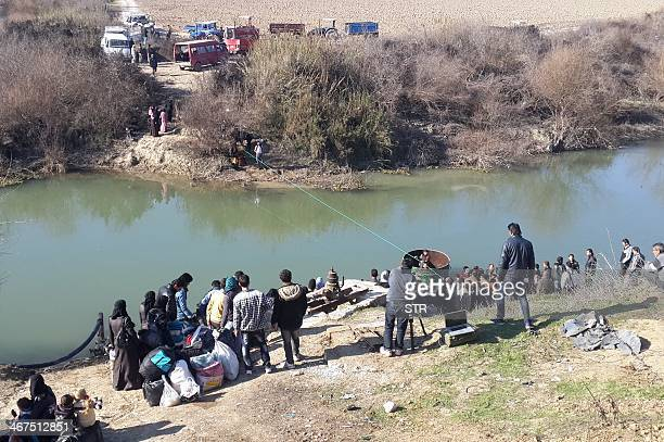 Displaced Syrians wait to cross the Orontes river into Turkey on February 5 2014 at the SyrianTurkish border in the Idlib province More than 130000...