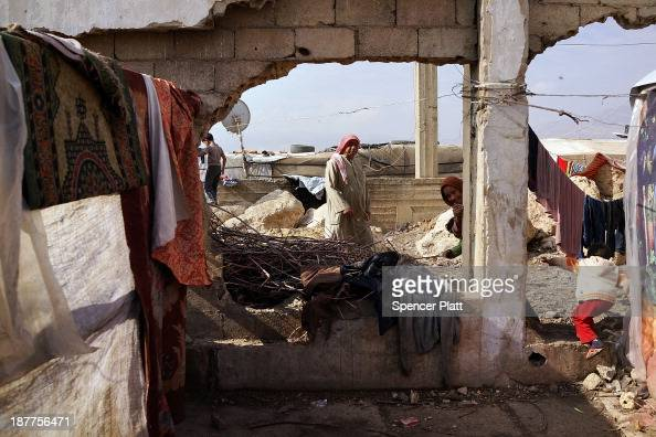 Displaced Syrians walk through a makeshift camp for Syrian refugees only miles from the border with Syria in the Bekaa Valley on November 12 2013 in...