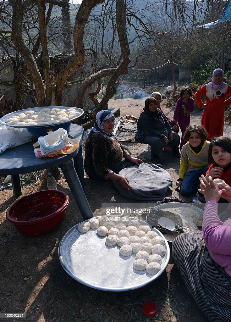 Displaced Syrians who fled their homes amid escalating violence prepare dough to make bread in the northern town of Darkush on January 25, 2013. More than 60,000 people have been killed in violence across Syria since an anti-regime revolt morphed into an armed insurgency after the regime of President Bashar al-Assad launched a brutal crackdown on dissent.