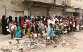 Displaced Syrians who fled their houses due to the ongoing conflict in Syria queue up to receive aid food in the rebel side of the northern city of...