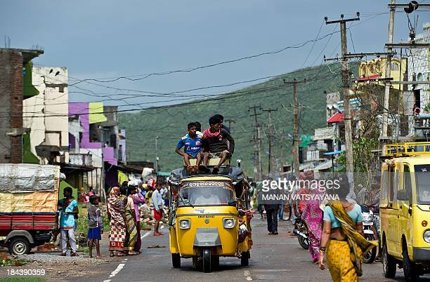 Displaced villagers ride on topof an autorickshaw as they return to Sonepur village in Gopalpur on October 13 2013 after cyclone Phailin passed...