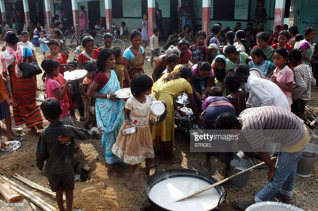 Displaced villagers wait to receive food at a relief centre following violence at Goraimari in Goalpara district, some 135 km from Guwahati in India's northeastern state of Assam, on February 13, 2013. India deployed hundreds of troops and imposed a curfew on Wednesday as the death toll from electoral violence in the northeastern state of Assam climbed to 20.
