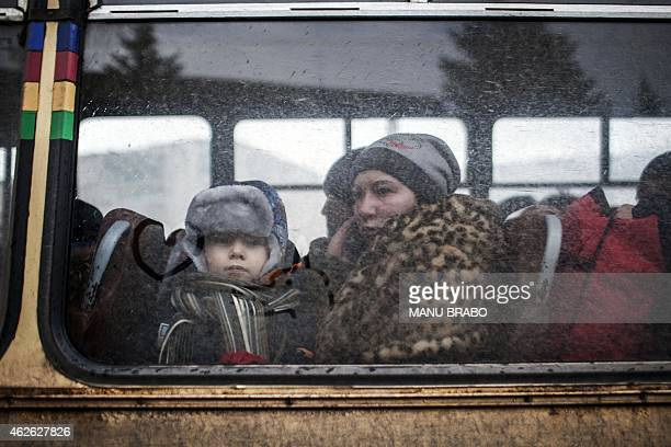 A displaced woman and a young boy sit in a bus before fleeing the Ukrainian city of Debaltseve in the Donetsk region on February 1 2015 Civilians...