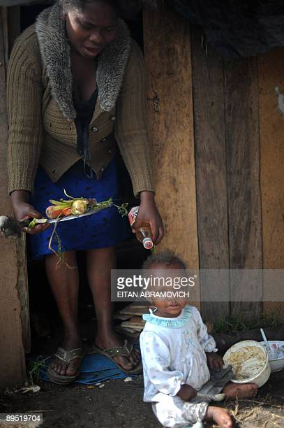 A displaced woman and her baby are seen outside their scrap wood shack at a makeshift camp at the Parque Tercer Milenio in downtown Bogota on July 30...