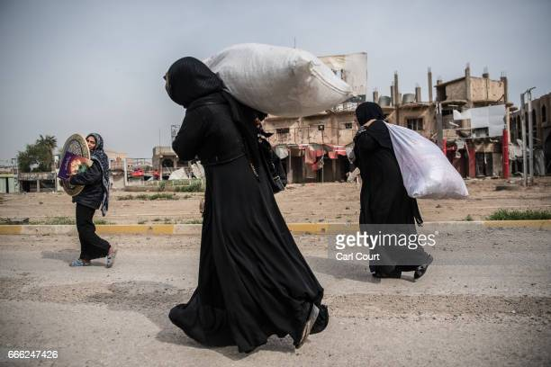 Displaced women carry possessions as they flee from their homes during fighting in west Mosul on April 8 2017 in Mosul Iraq Despite air support from...