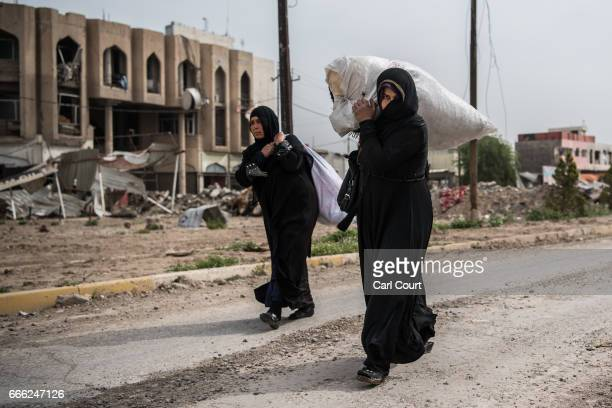 Displaced women carry their belongings as they flee from their homes during fighting in west Mosul on April 8 2017 in Mosul Iraq Despite air support...