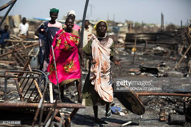 Displaced women residing in the United Nations Protection of Civilians site in Malakal examine a burnt and looted area searching for their belongings...