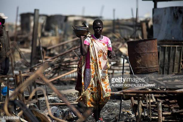A displaced women residing in the United Nations Protection of Civilians site in Malakal examines a burnt and looted area searching for her...