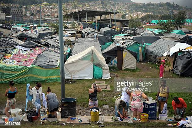 Displaced women wash themselves while others do the laundry at a makeshift camp at the Parque Tercer Milenio in downtown Bogota on July 30 2009 More...