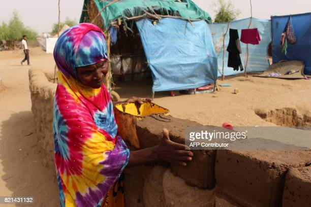 A displaced Yemeni woman who fled the fighting between the Saudiled coalition and Shiite Huthi rebels in the area of Harad builds a mud wall at a...