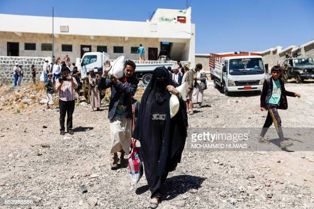 Displaced Yemenis carry sacks of food supplies distributed by the Russian humanitarian relief mission at a camp on the outskirts of the capital Sanaa...