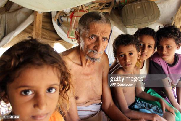 Displaced Yemenis who fled the fighting between the Saudiled coalition and Shiite Huthi rebels in the area of Harad sit under a makeshift shelter at...