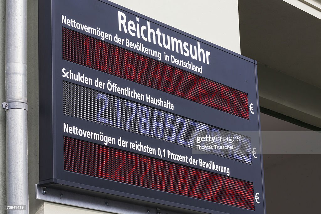Display board with the inscription wealth clock, which displays net assets of the German population on March 05, 2014 in Berlin, Germany. This display board is mounted on an exterior wall of a house in Berlin.