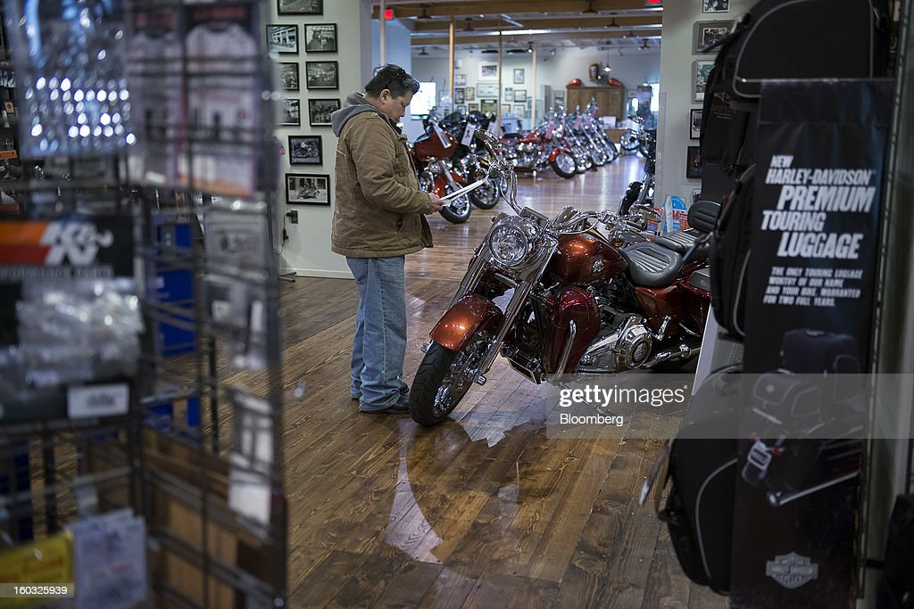 A display for Harley-Davidson Inc. luggage stands at right while a customer looks at a motorcycle on the showroom floor at the Dudley Perkins Co. dealership in South San Francisco, California, U.S., on Monday, Jan. 28, 2013. Harley-Davidson reported fourth quarter revenue of $1.17 billion. Photographer: David Paul Morris/Bloomberg via Getty Images