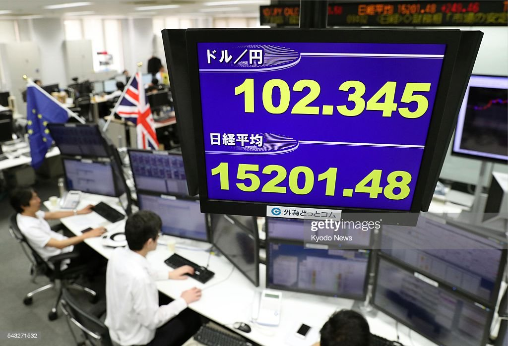 A display in the Tokyo office of a foreign exchange dealer shows the dollar trading in the 102 yen range and Japan's key Nikkei stock index at the 15,200 level in the early morning of June 27, 2016. Japanese stocks moved higher after they plunged on June 24 following the British decision to leave the European Union in a referendum.