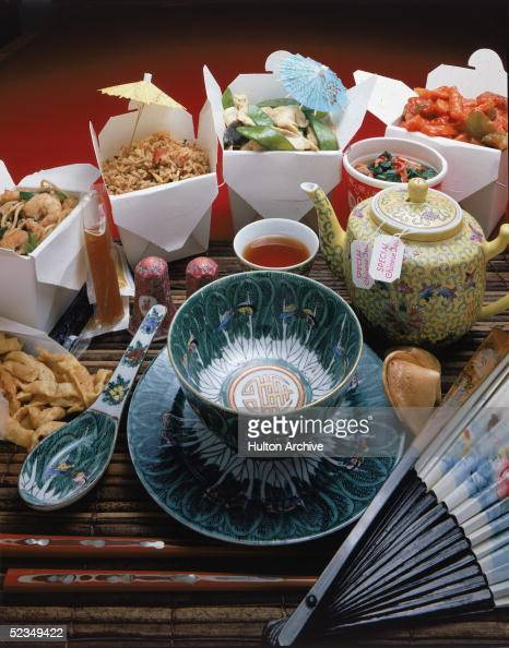 A display of Chinese takeout food and appropriate serving and eating items includes a Chinesetheme patterned bowl saucer and soup spoon condiments a...
