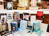 A group of modern fiction books is on display in a book store window.
