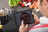 Display of digital tablet reflecting mirror image of smiling man in a kitchen
