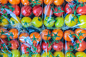 Display of fresh plastic wrapped yellow, orange and red cherry tomatoes