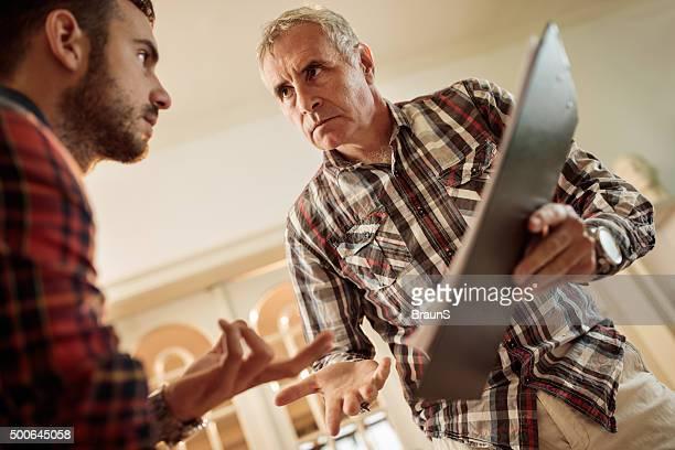Contrarié Homme d'affaires parlant à son collègue de documents.