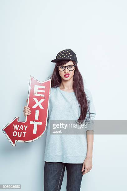 Displeased contemporary girl holding exit sign