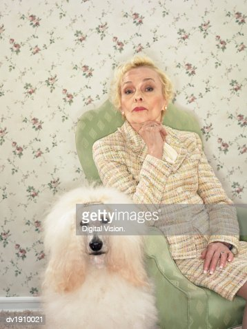 Displeased Looking Woman Sitting on an Armchair With a Poodle Next to Her