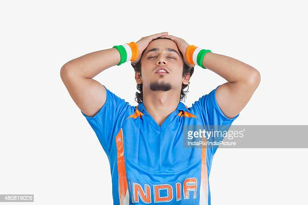 Displeased man in Indian cricket team jersey with hands on head over white background