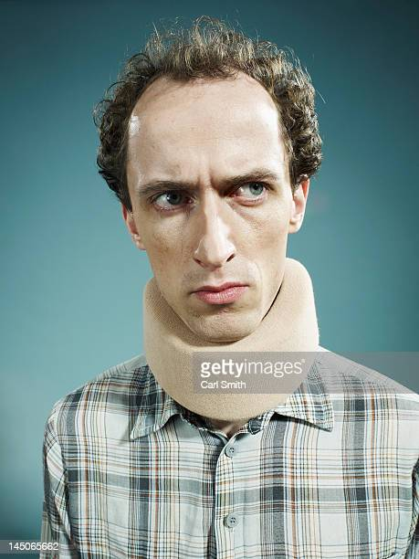 A displeased man wearing a neck brace and looking suspiciously to the side