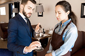 Serious pernickety handsome restaurateur with beard pointing at wineglass and lecturing upset waitress in apron in high quality restauran