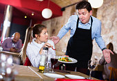 Displeased aggressive young woman conflicting with apologetic waiter because of poor quality of dish in restaurant
