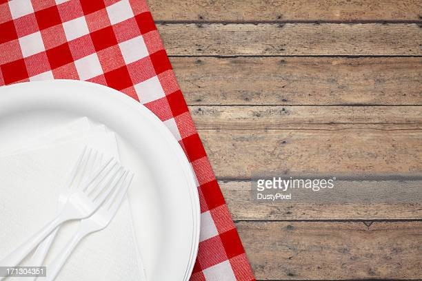 Disposable plate and forks with red and white picnic cloth