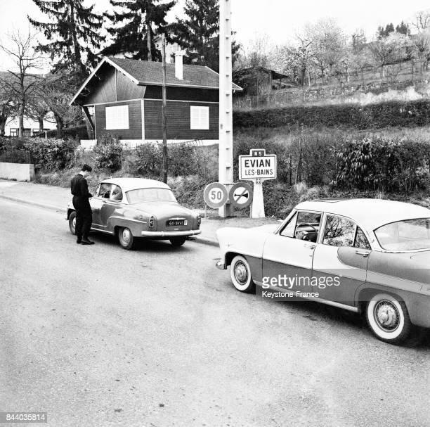 Dispositif de sécurité aux abords de la ville un policier arrête les voiture et vérifié les papiers des conducteurs à Evian France en 1961