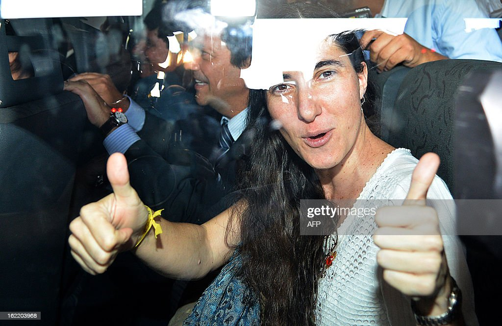 Dissident Cuban blogger Yoani Sanchez gives her thumbs up upon her arrival at the National Congress, in Brasilia, on February 20, 2013. Sanchez is on an 80-day tour, after she got a passport two weeks ago under Cuba's sweeping immigration reform that went into effect this year. The 37-year-old philologist, who found an international audience on the Internet with her prize-winning blog 'Generation Y,' is known for her biting commentary, which has drawn the displeasure of Cuba's ruling communist party. AFP PHOTO/Pedro LADEIRA