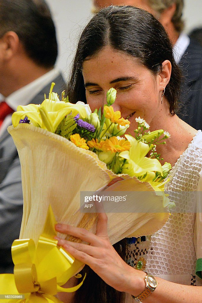 Dissident Cuban blogger Yoani Sanchez receives a bunch of flowers during her visit to the Chamber of Deputies, at the National Congress in Brasilia, on February 20, 2013. Sanchez is on an 80-day tour, after she got a passport two weeks ago under Cuba's sweeping immigration reform that went into effect this year. The 37-year-old philologist, who found an international audience on the Internet with her prize-winning blog 'Generation Y,' is known for her biting commentary, which has drawn the displeasure of Cuba's ruling communist party. AFP PHOTO/Pedro LADEIRA